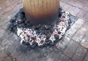 placing hot charcoal around perimeter of trash can turkey