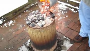 pouring hot charcoal on top of garbage can
