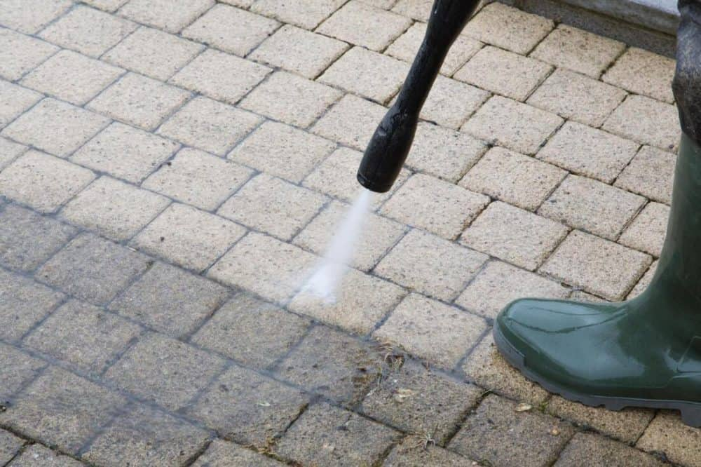 a power washing cleaning a brick patio