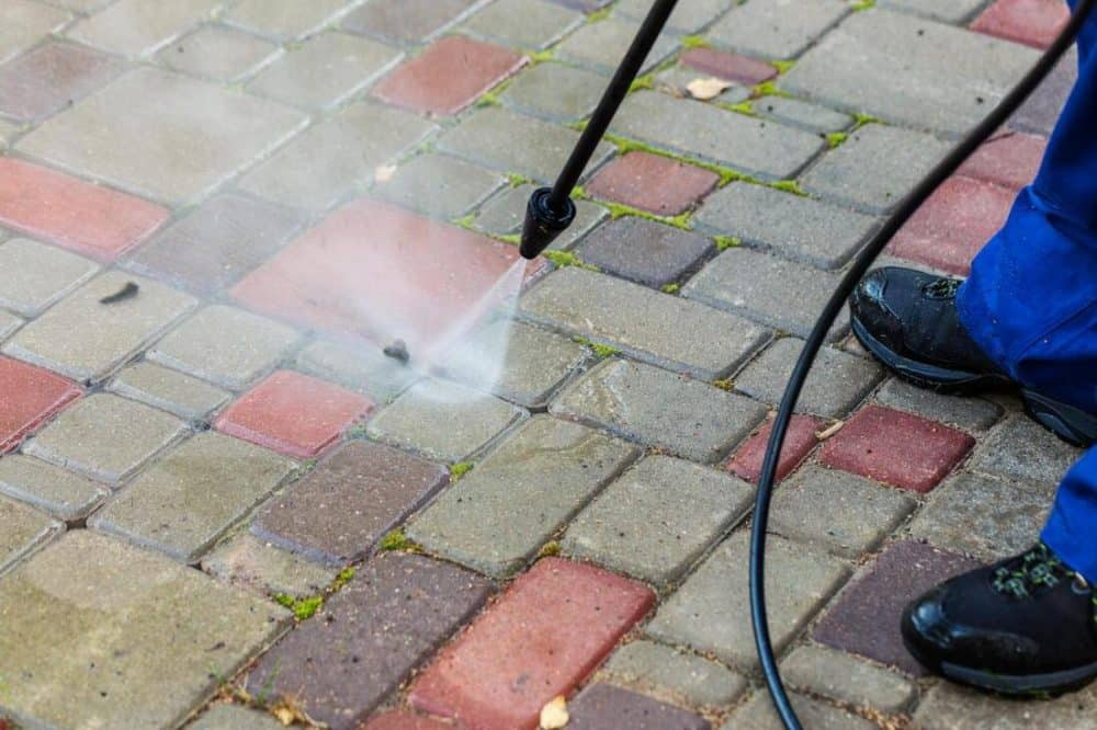 cleaning a brick patio with a power washer