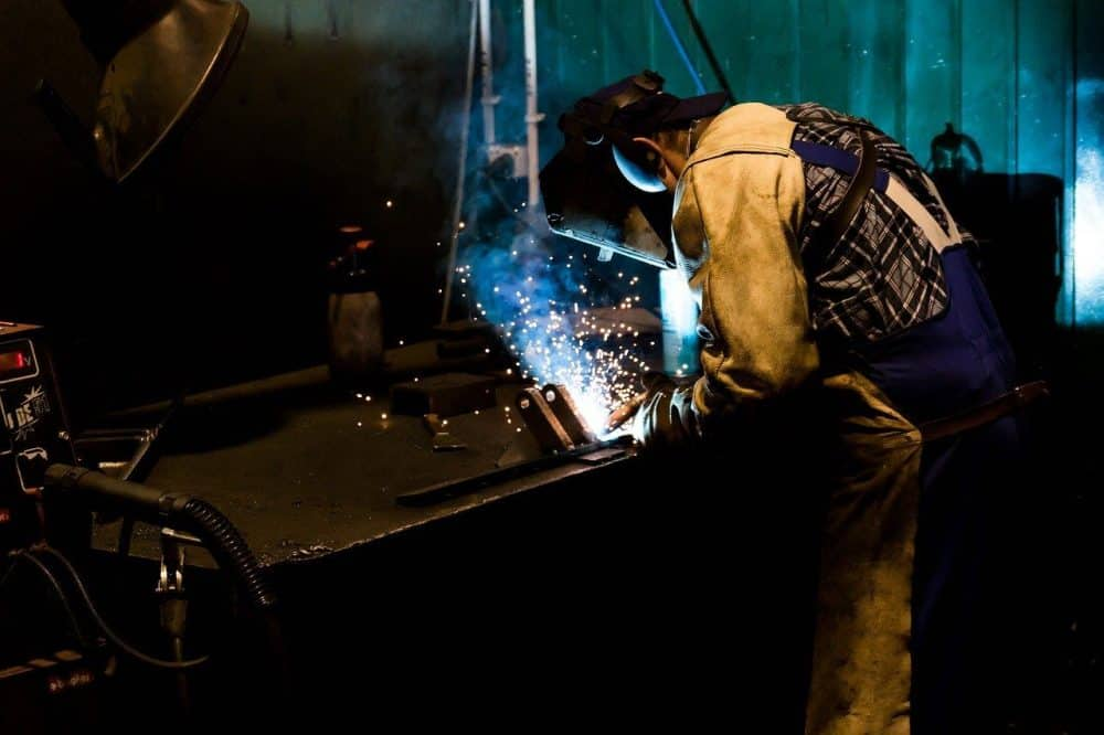 a welder creating and joining peices of an oil tank smoker he has built