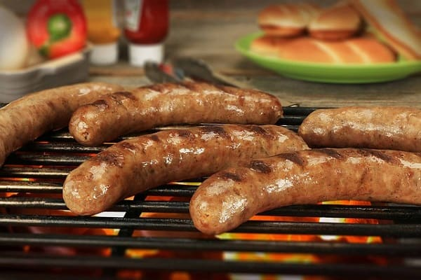 brats grilling on a propane grill