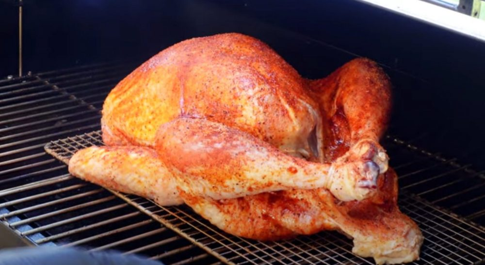 a turkey cooking on a pellet grill