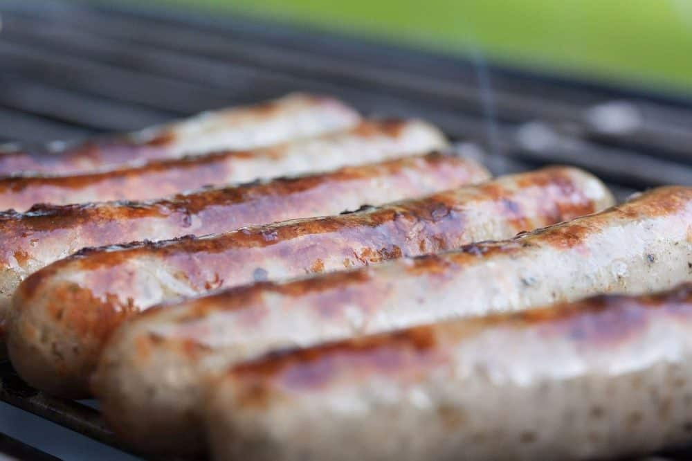 intact casings on brats on a propane grill