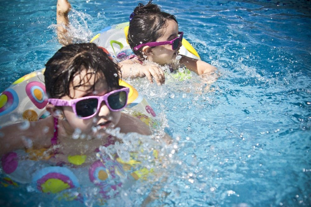 kids swimming in a pool with safe chlorine levels
