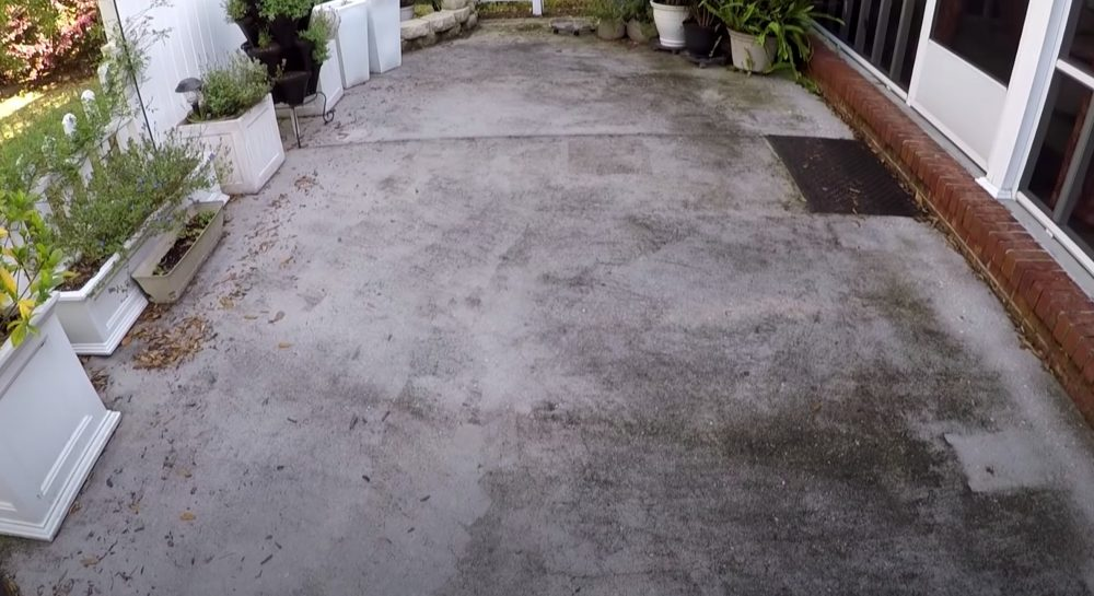 a dirty concrete patio that needs to be cleaned