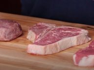 a cutting board comparing a filet mignon with a new york strip steak