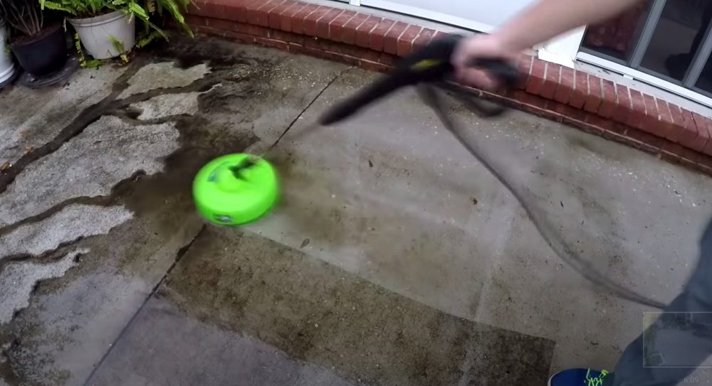 a sun joe cleaning a concrete patio without a pressure washer