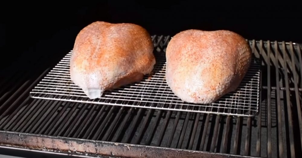 2 raw turkey breasts starting to cook on a pellet grill