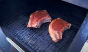 pork chops being placed on a pellet grill smoker
