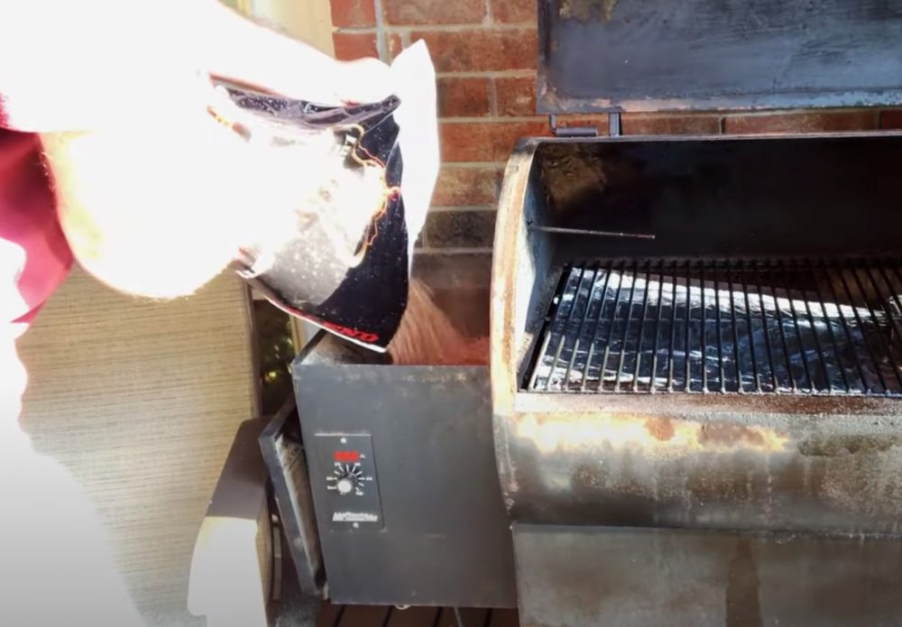 pouring pellets into a traeger pellet grill hopper