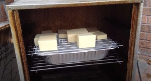smoked cheese sitting on an ice tray in a masterbuilt electric smoker