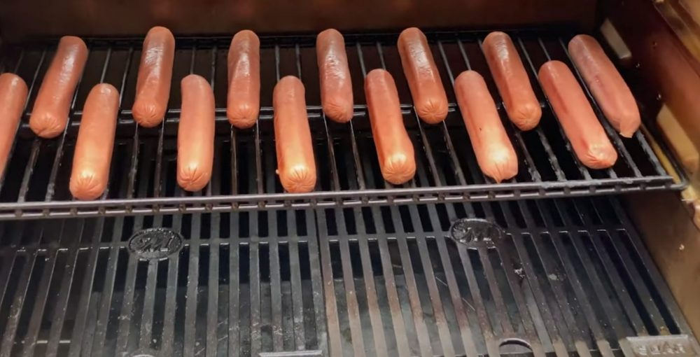 putting hot dogs on a smoker