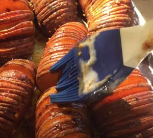 basting butter on smoking sweet potatoes while cooking