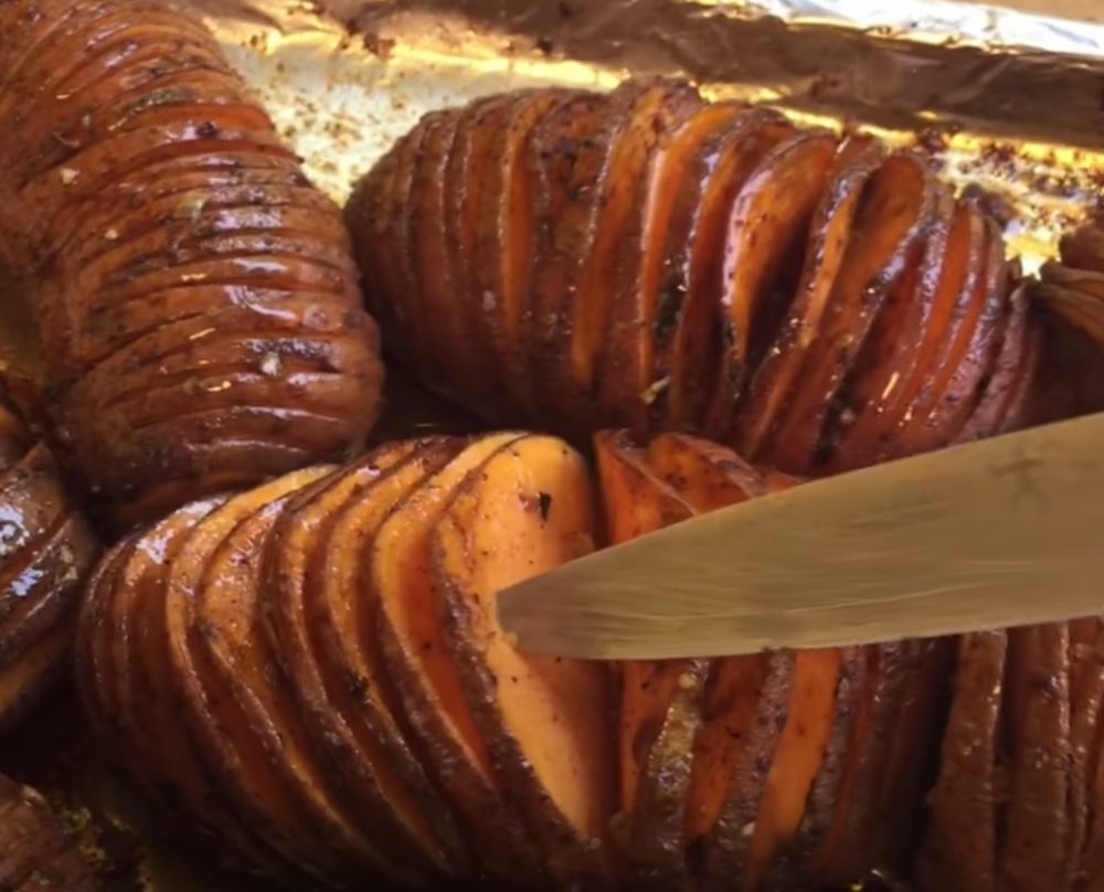 checking doneness of the cooked and smoked sweet potatoes
