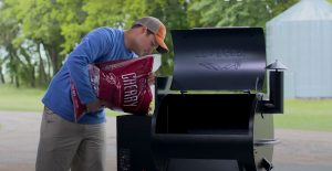 pouring pellets into the hopper of a traeger pellet grill before seasoning