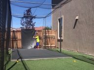 kids playing in a homemade batting cage