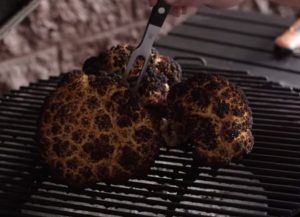 poking smoked cauliflower with fork to check doneness