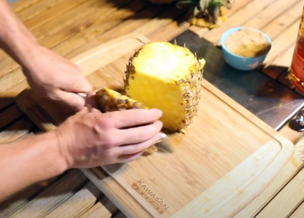 slicing the outer skin off a pineapple to smoke
