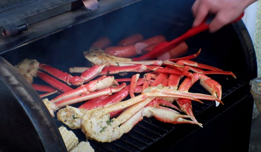 basting butter on smoked crab legs on a pellet grill
