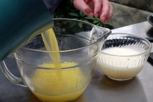 pouring clarified butter for smoked crab legs into a bowl