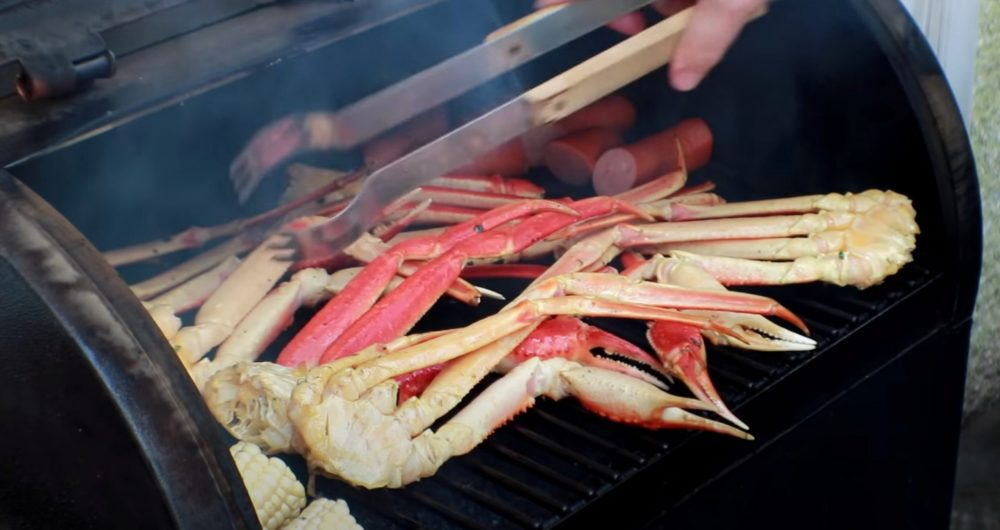 flipping over smoked crab legs on a pellet grill